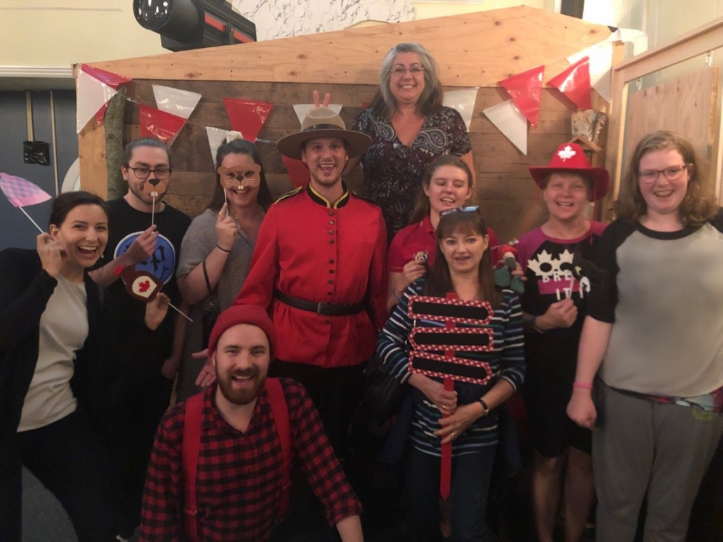 A group of teens and adults stand with a man in a mountie costume.